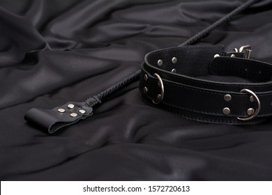 Stack for BDSM games and leather collar on black silk background. Accessories for adult sexual game. Domination concept