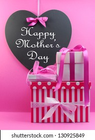 Stack of beautiful pink stripe and polka dot present gifts with heart shape blackboard with Happy Mothers Day message.