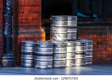 Stack of beer barrels on the sidewalk in front of a wall of red stone. Dublin, Ireland, Europe.