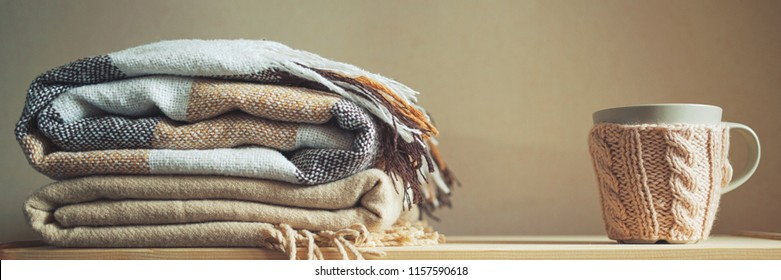 stack of beige checkered wool blankets and cup on a wooden chest. autumn - winter concept of home warmth and comfort. toned, long banner