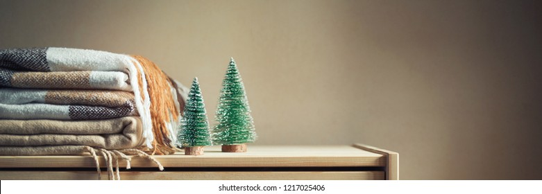 stack of beige checkered wool blankets and two Christmas trees on a wooden chest. Cozy winter still life. Home textile. Long banner, copy space