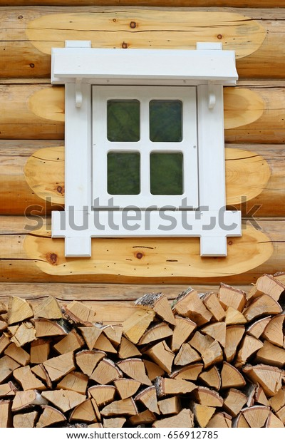 Stack of birch and pine under white window