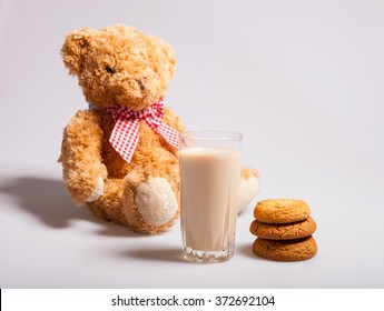 A stack of biscuits, a glass of milk, a toy bear