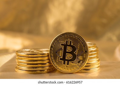 Stack of bitcoins with gold background with a single coin facing the camera in sharp focus with shading on the icon letter B on the face of the bit coin