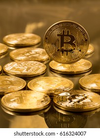 Stack of bitcoins with gold background with a single bit coin floating above the rest in sharp focus with the bitcoin symbol prominent
