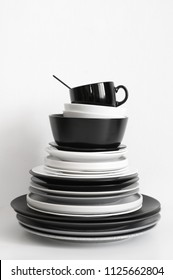Stack of black and white tableware on white background.