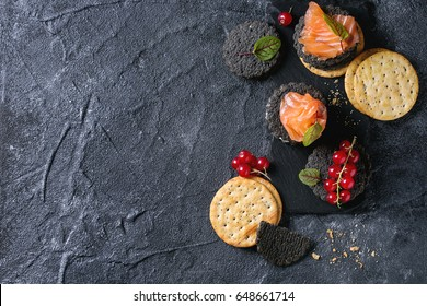 Stack of black wholegrain charcoal and traditional crackers with smoked salmon, cream cheese, green salad and red currant berries on slate board over black stone background. Appetizer snack. Top view