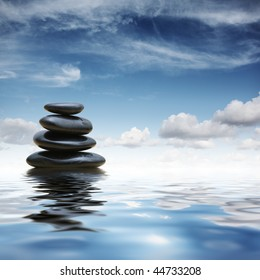 Stack of black zen pebble stones reflecting in water over blue sky background