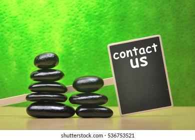 Stack of black zen and spa stone with green background with word contact us