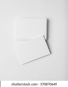 Stack of blank business cards on white background with soft shadows. Vertical
