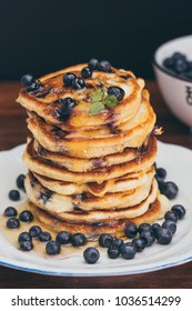 Stack of bluberry pancakes with honey and fresh bluberries