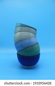 stack of blue ceramic soup bowls on a turquoise background, isolated. vertical image, minimalist concept