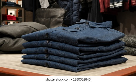 Stack of blue denim shirts on table in clothing store