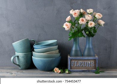 Stack of blue handmade ceramic bowls, mugs and pink roses bouquet in rustic vase against dark gray wall.