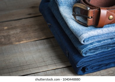Stack of the blue jeans and brown genuine leather belt on wooden background. close up.