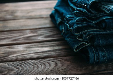 Stack of blue jeans denim pants on a wooden table.