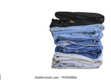 Stack of blue jeans on white background with copy space