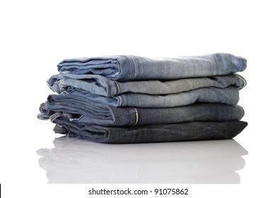 Stack of blue jeans on a white background, perfect reflection