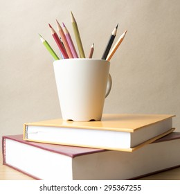 stack of book with color pencil on wood table background