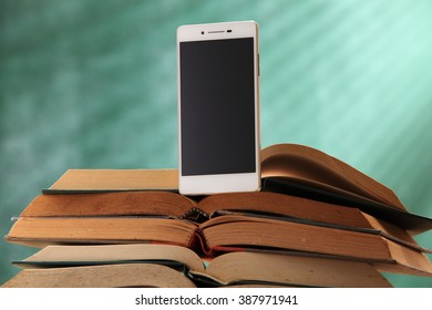 stack of book and smart phone in front of black board