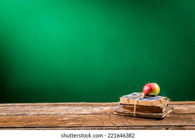 Stack of books and an apple in a classroom