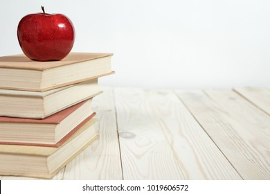 Stack of books and apple on the table. Copy space for text. Selective focus. Knowledge concept