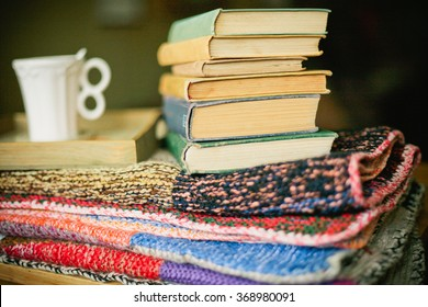 Stack of books and cup on old knitted blanket