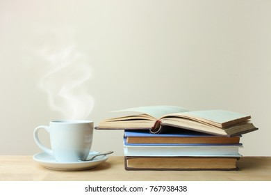 A stack of books and a cup of tea on a wooden table on a neutral background.