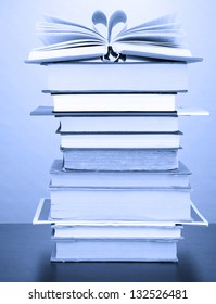 Stack of books in dark blue light