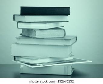 Stack of books in dark green light
