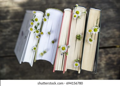 A stack of books with flowers between pages on a wooden rural table