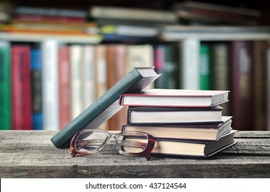 Stack of books and glasses on wooden table with bookshelf, invitation to study literatures, close up, reading room