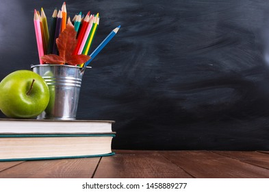 Stack of books, green apple, colored pencils and autumn leaf on wooden desk. Classroom blackboard with copy space in background. Education, back to school concept - Shutterstock ID 1458889277