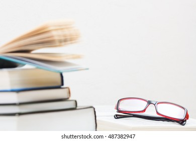 Stack of books in hardcover and glasses on the table