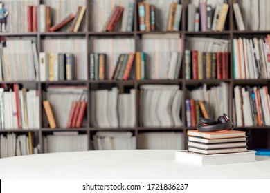 A stack of books with headphones on the background of a rack of books in the reading room of the library. Student poster