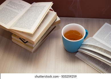 a stack of books and a hot drink in a blue mug on wooden table,