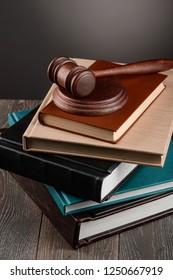Stack of books and judge's gavel on wooden table. Judiciary education and law career.