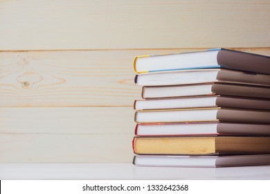 A stack of books lying on the table on a light wooden background. Back to school. Education background.