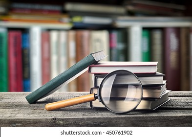 Stack of books and magnifier on wooden table with bookshelf, invitation to study literatures, close up, reading room