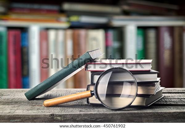 Bücherstapel und Lupe auf Holztisch mit Bibliothek, Einladung zum Lernen von Literatur, Nahaufnahme, Lesesaal