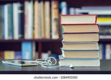 A stack of books and mobile phone with headphones on the background of bookshelves.