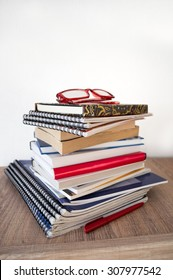 stack of books, notebooks and glasses on wooden shelf