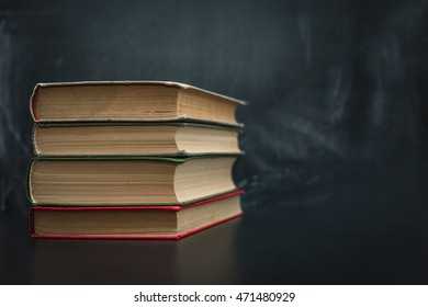 A stack of books on black background blackboard