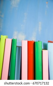 Stack of books on a blue background. A lot of books are close-up.