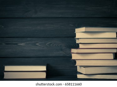 Stack books on dark wooden background. Reading concept.