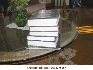 stack of books on glass table