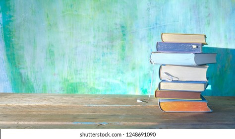 stack of books on green grungy background, panoramic, good copy space