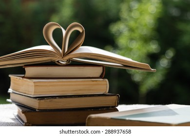 stack of books on table in garden with top one opened and pages forming heart shape