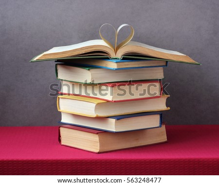 stack of books on the table with a red tablecloth. an open book with curled leaves laying on top. love of books.