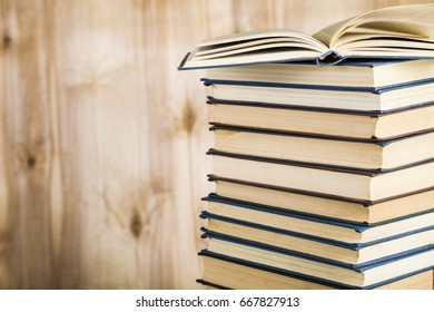 Stack of books on a wooden background. Stack of books with an open book on top of a close-up